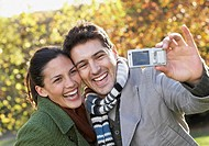 Couple outdoors taking a picture of themselves with camera phone