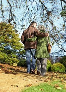 Couple outdoors arm in arm on a path in a park
