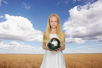 Young girl outdoors in a field holding a silver globe