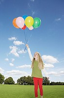 Young girl outdoors holding balloons at a park