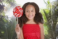 Young girl outdoors holding lollipop