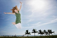 Young girl outdoors at the beach jumping