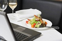 Salad with bacon in front of laptop on restaurant table