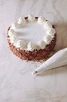 Buttercream cake with grated chocolate, piping bag beside it