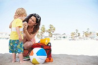 Mid adult woman with son 2-3 on beach