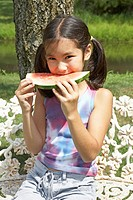 Girl 8-9 eating slice of watermelon outdoors, portrait