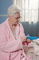 Senior woman looking at pill box sitting on bed