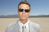 Businessman wearing sunglasses in dry lake bed, close-up