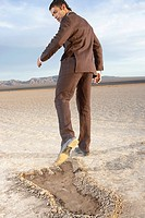 Businessman looking back at large footprint in dry lake bed, rear view