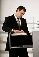 Businessman looking in file cabinet in office
