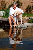 senior woman with dog at pond
