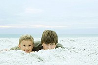 Two brothers lying on the beach together, both smiling at camera, portrait