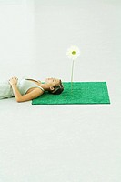 Woman lying with head on square of artificial turf