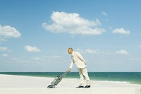 Man in suit using vacuum cleaner on beach, full length