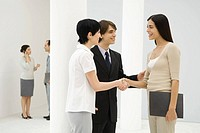Two businesswomen standing beside male colleague, shaking hands, smiling at each other