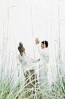 Two men greeting each other outdoors, hands raised, viewed through tall grass