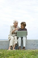 Senior woman and grandson sitting outdoors, using laptop computer together