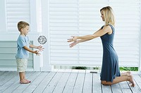 Mother and son face to face, throwing ball, side view