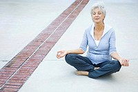 Senior woman sitting in lotus position, eyes closed