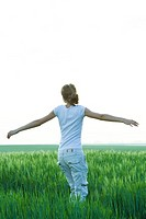 Teenage girl standing in field with arms outstretched, rear view