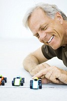 Mature man playing with toy cars, smiling, close-up
