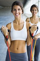 Teenage twin sisters exercising with resistance bands, both smiling at camera