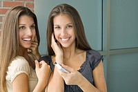 Teenage twin sisters listening to mp3 player together, both smiling, one looking at camera