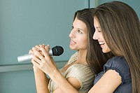 Teenage twin sisters singing into microphone together, side view