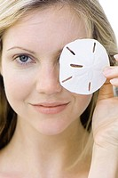 Woman covering one eye with sand dollar, smiling at camera, portrait