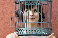 Woman holding empty birdcage in front of face, smiling, looking away (thumbnail)