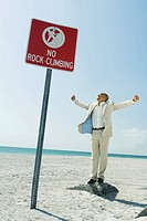 Man standing on top of rock at beach, no rock climbing sign in foreground