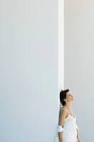 Woman leaning against wall, head back, eyes closed, side view (thumbnail)
