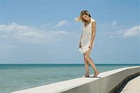 Young woman in sundress standing on low wall beside sea, eyes closed (thumbnail)