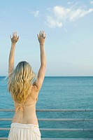 Woman standing at railing by the sea, arms raised, rear view