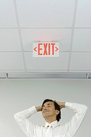 Man beneath exit sign with eyes closed, hands on head, smiling, low angle view