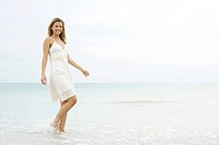 Young woman in sundress walking in shallow water, smiling at camera