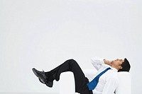 Businessman lying sideways in armchair, making phone call, full length