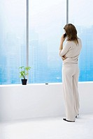 Woman standing by window, using cell phone