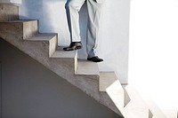 Businessman standing on staircase, low section, low angle view