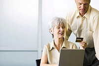 Couple using laptop computer, woman holding up credit card