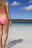 Woman in bikini standing in a beautiful lake, seen from behind. Fraser Island, Australia