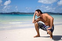 Man crouching on beach.  Whitehaven Beach, Australia