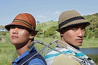 Portrait of two young men with their golf clubs (thumbnail)
