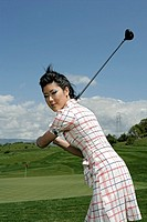 Portrait of a young woman posing with a golf club