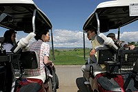 View of couples talking from their golf carts