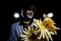 Young man holding large paper sunflowers