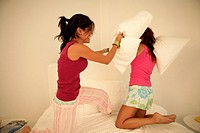 Two females engage in a pillow fight