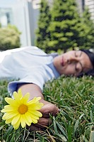 View of a woman sleeping on the grass and holding a flower