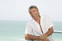 Mature married man smiling on a terrace (thumbnail)