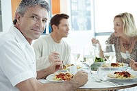 Three mature adults eating, one man looking at camera